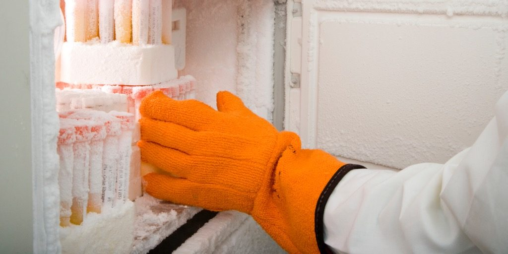 Researcher's arm retrieving medical samples from freezer.